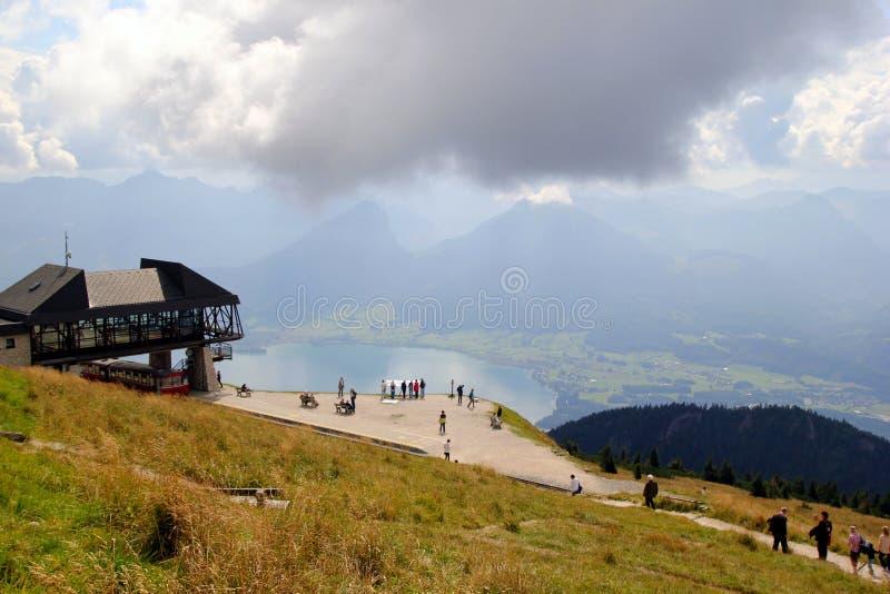 La opinión sobre las montañas y un lago con la gente que camina fotos de archivo libres de regalías