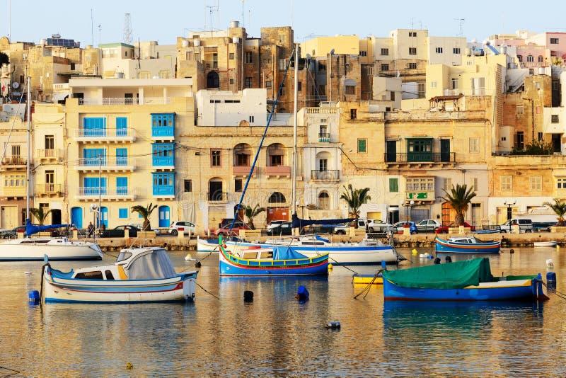 La opinión sobre los barcos malteses tradicionales en puesta del sol fotos de archivo