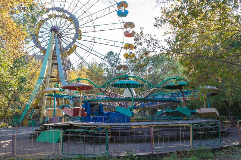 La opinión sobre la noria, la zona del juego y del resto en el parque de la ciudad, llamó Kio Cubierto por los árboles, las flore foto de archivo libre de regalías