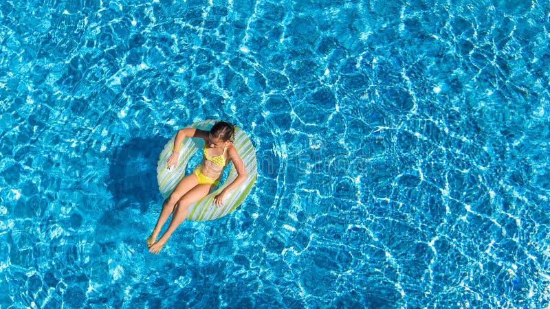 La opinión superior aérea la muchacha en piscina desde arriba, niño nada en el buñuelo inflable del anillo, niño se divierte en a imagen de archivo