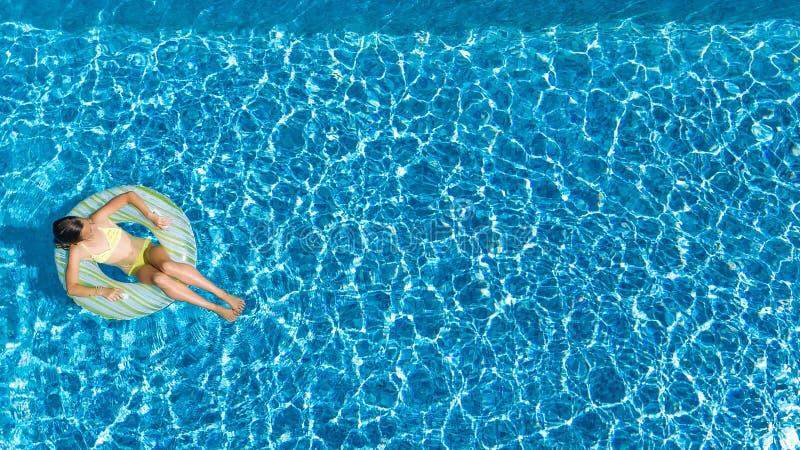 La opinión superior aérea la muchacha en piscina desde arriba, niño nada en el buñuelo inflable del anillo, niño se divierte en a fotos de archivo libres de regalías