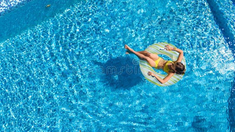 La opinión superior aérea la muchacha en piscina desde arriba, niño nada en el buñuelo inflable del anillo, niño se divierte en a fotografía de archivo libre de regalías