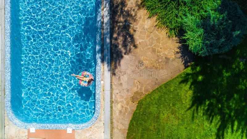 La opinión superior aérea la muchacha en piscina desde arriba, niño nada en el buñuelo inflable del anillo, niño se divierte en a imagen de archivo libre de regalías