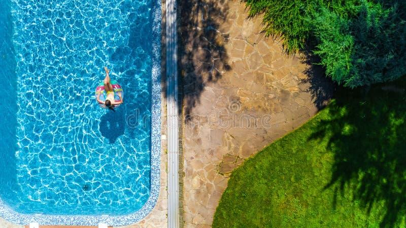 La opinión superior aérea la muchacha en piscina desde arriba, niño nada en el buñuelo inflable del anillo, niño se divierte en a fotos de archivo