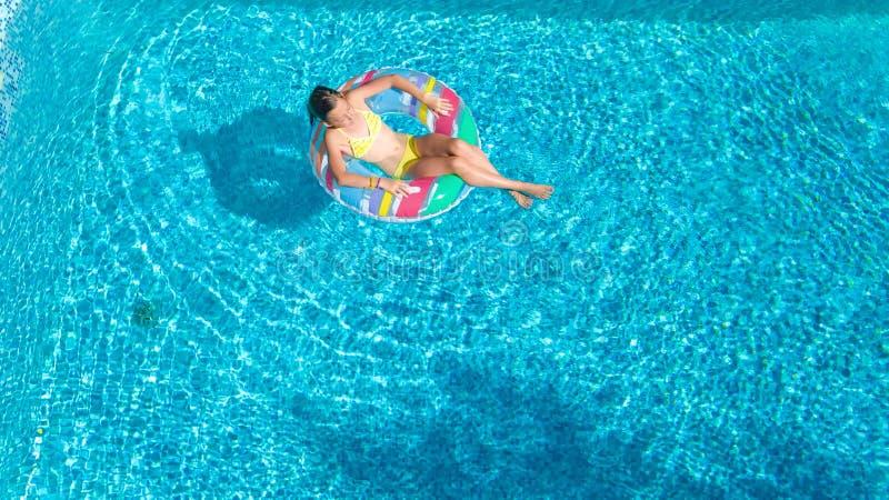 La opinión superior aérea la muchacha en piscina desde arriba, niño nada en el buñuelo inflable del anillo, niño se divierte en a foto de archivo libre de regalías