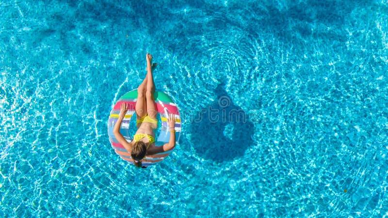 La opinión superior aérea la muchacha en piscina desde arriba, niño nada en el buñuelo inflable del anillo, niño se divierte en a imágenes de archivo libres de regalías
