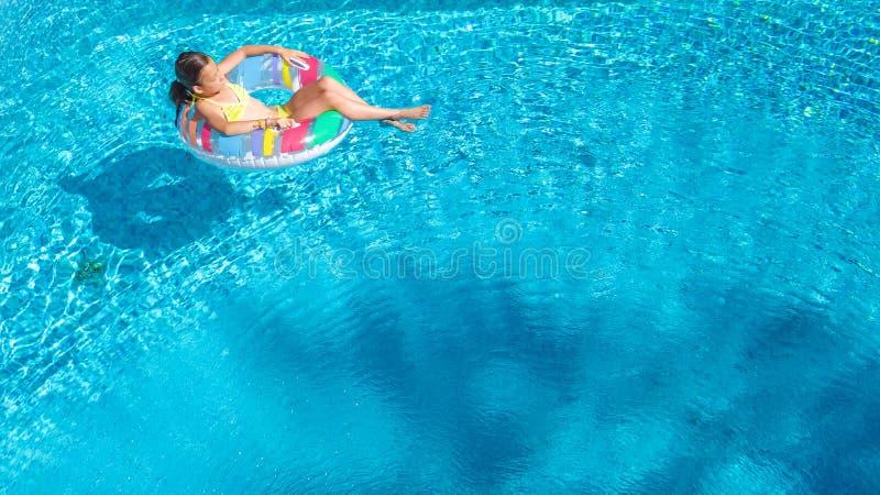 La opinión superior aérea la muchacha en piscina desde arriba, niño nada en el buñuelo inflable del anillo, niño se divierte en a imagenes de archivo