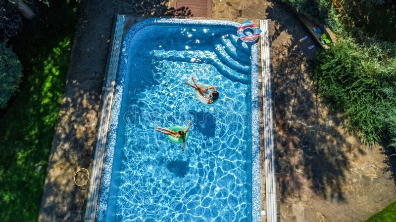 La opinión superior aérea niños en piscina desde arriba, los niños felices nada en los anillos de espuma inflables del anillo y s foto de archivo