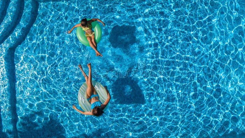 La opinión superior aérea niños en piscina desde arriba, los niños felices nada en los anillos de espuma inflables del anillo y s imagenes de archivo