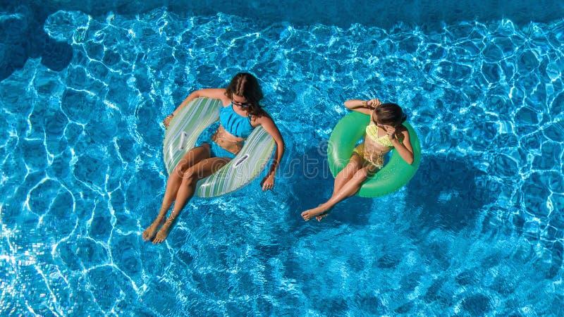 La opinión superior aérea niños en piscina desde arriba, los niños felices nada en los anillos de espuma inflables del anillo y s fotografía de archivo