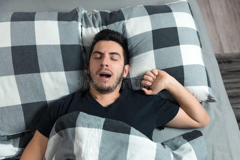 La opinión superior el hombre hermoso bosteza y frota sus ojos mientras que duerme imagen de archivo