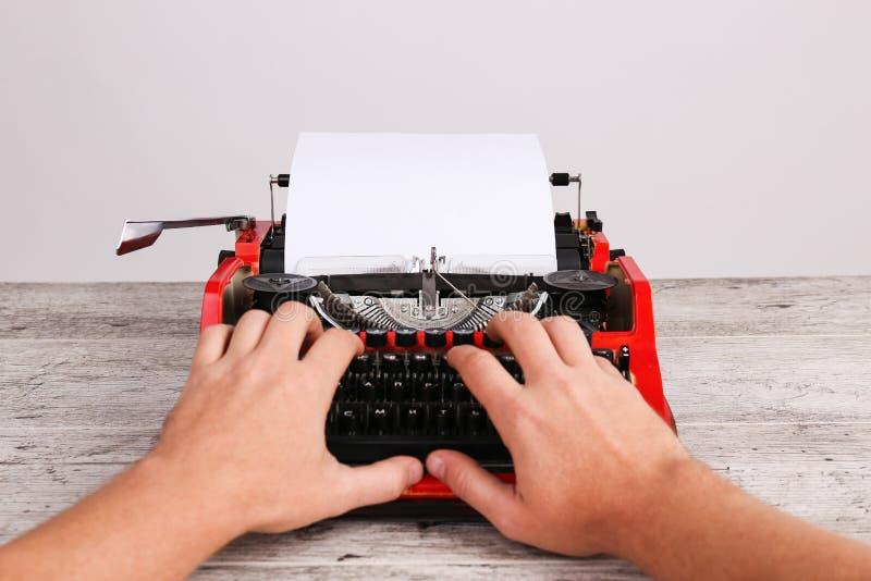 La opinión superior el hombre y la máquina de escribir vieja roja con el papel en blanco blanco cubren en la tabla gris foto de archivo libre de regalías
