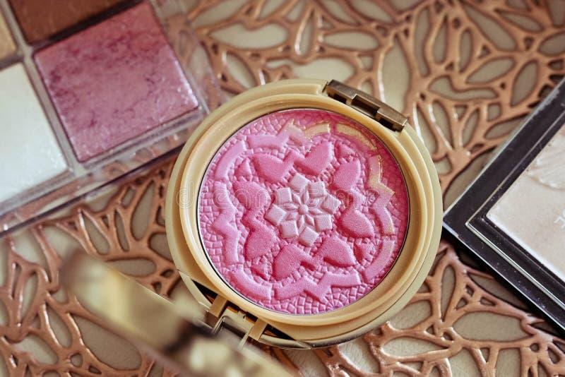 La opini?n superior la hembra compone el sistema con rosa se ruboriza paleta y caja del polvo en el fondo de oro hermoso foto de archivo
