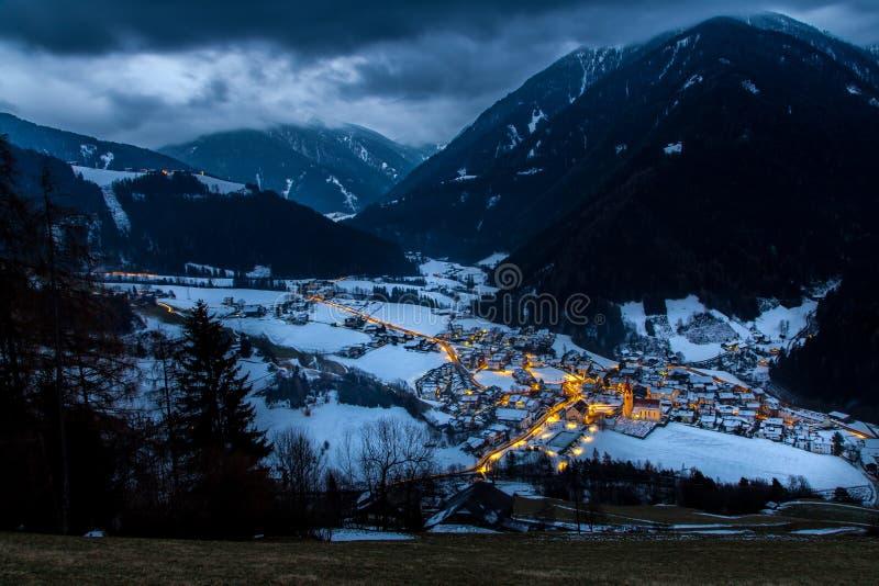 La opinión superior sobre pueblo nevoso luesen el valle en la noche el Tirol del sur él fotos de archivo libres de regalías