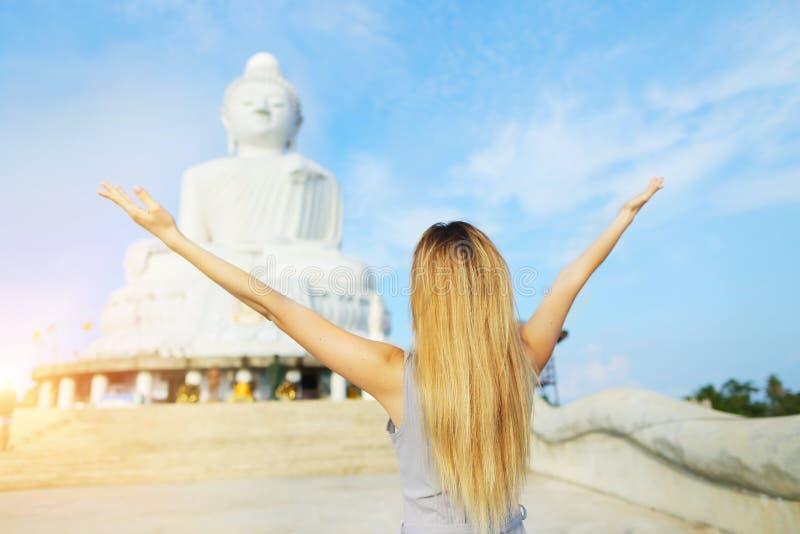 La opinión trasera la chica joven con las manos aumentadas acerca a la estatua de Buda en Phuket, Tailandia imágenes de archivo libres de regalías