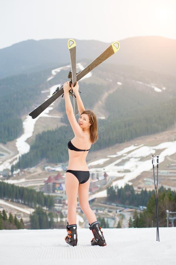 La opinión trasera el esquiador feliz de la mujer en el traje de baño que se coloca en la cuesta y que se sostiene esquía sobre l fotografía de archivo