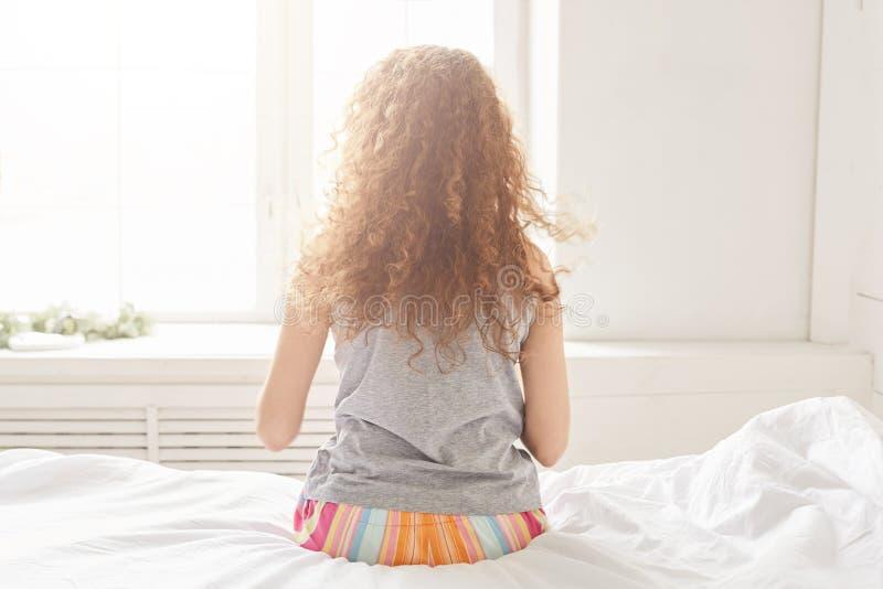 La opinión trasera la hembra joven rizada en pijamas se sienta en el lado de la cama, goza del sol de la ventana, admira mañana s foto de archivo