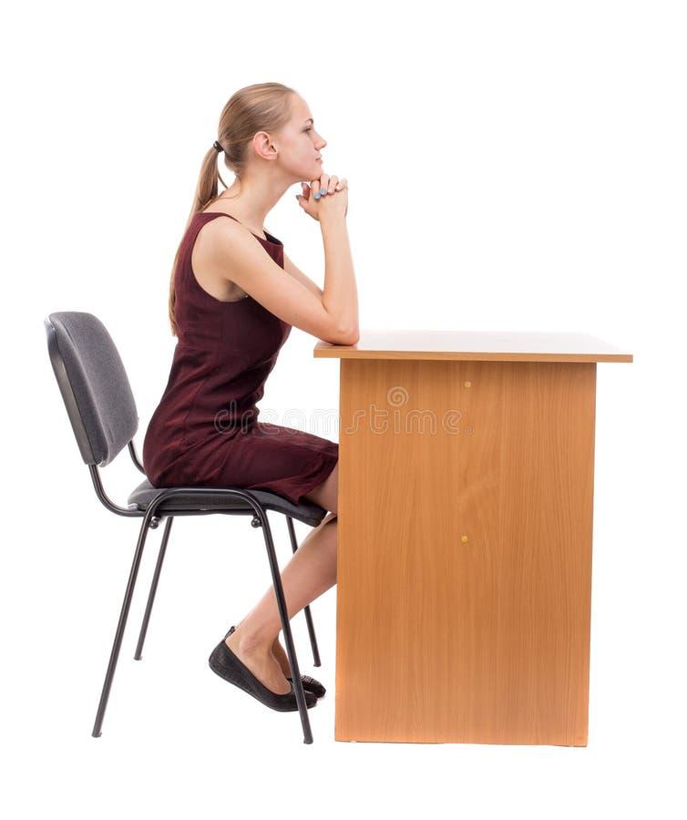 La opinión trasera la mujer se sienta por la tabla y mira fotografía de archivo