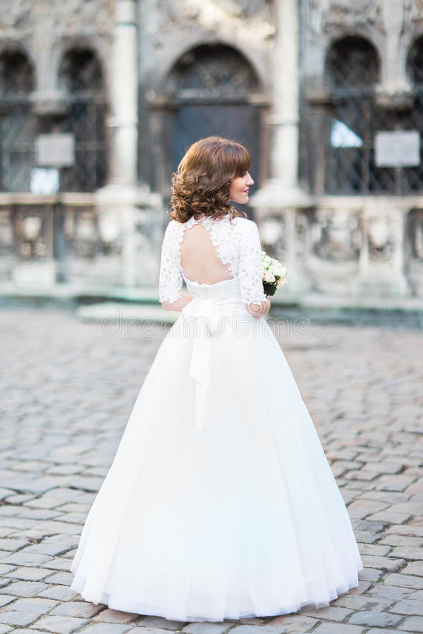 La opinión trasera la novia con el ramo de la boda en la calle imagenes de archivo