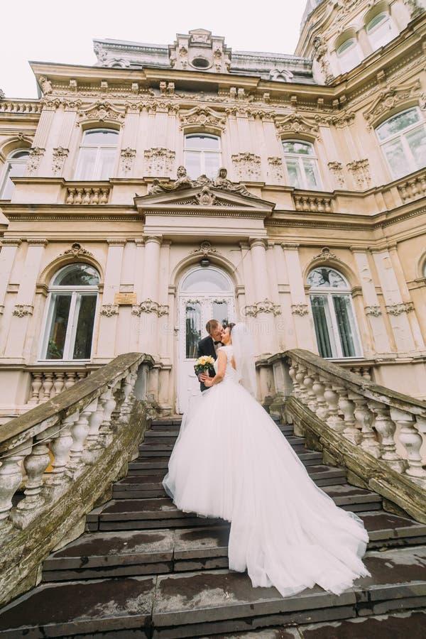 La opinión trasera los recienes casados felices que se colocan en las escaleras del edificio viejo El novio está besando a la nov fotos de archivo libres de regalías