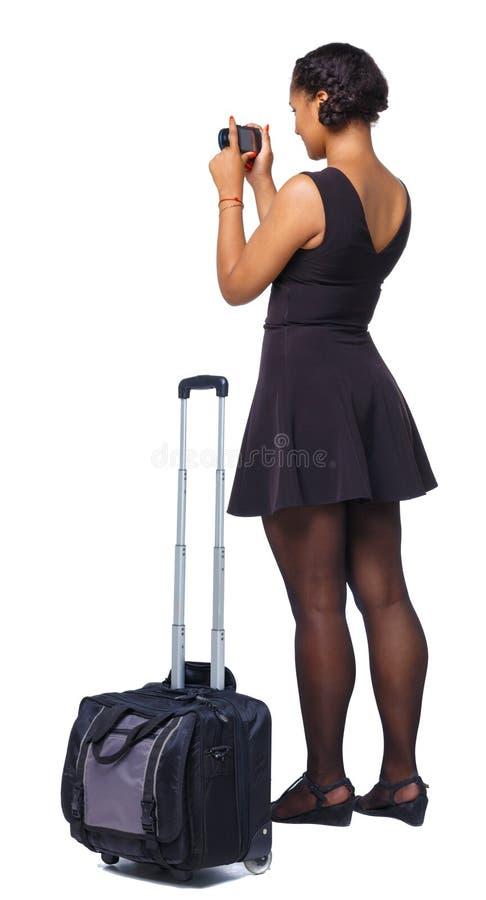La opinión trasera la mujer negra elegante vestida con la maleta hace las fotos en la cámara imágenes de archivo libres de regalías