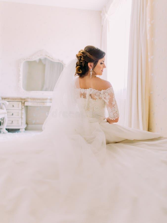 La opinión trasera la novia preciosa que se sienta en la cama fotos de archivo