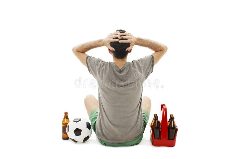 La opinión trasera un hombre joven con el balón de fútbol y el paquete del partido de fútbol de observación de la cerveza, parece imágenes de archivo libres de regalías