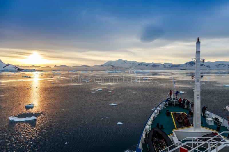 La opinión y la gente de la puesta del sol recolectaron en la cubierta, deriva de los icebergs foto de archivo libre de regalías