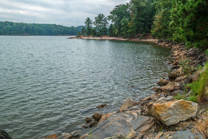 La orilla del lago con rocas y árboles fotografía de archivo libre de regalías