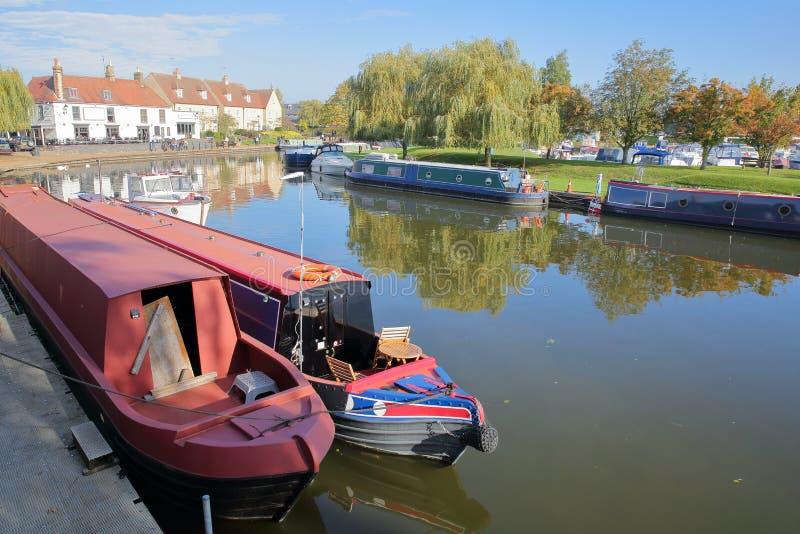La orilla en otoño con las gabarras amarradas en el río Great Ouse y las casas tradicionales, Ely, Cambridgeshire foto de archivo