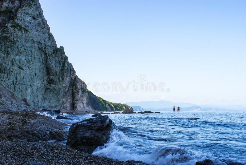 La orilla rocosa del mar es afianzada con abrazadera sobresaliendo por rocas Onda que lava la piedra Opini?n los hermanos de la r foto de archivo libre de regalías