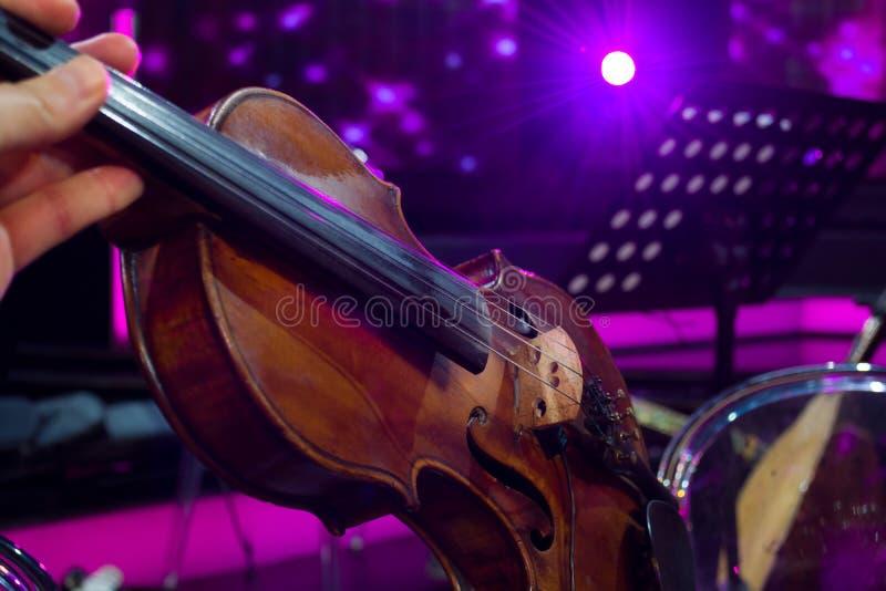 La orquesta en violín del ensayo y fondo ligero magenta fotos de archivo