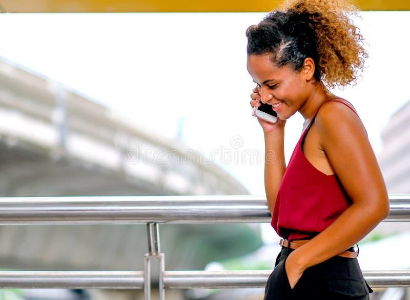 La oscuridad broncea a la mujer de la raza mixta de la piel con llamada sonriente alguien y habla con su teléfono móvil, también  fotos de archivo