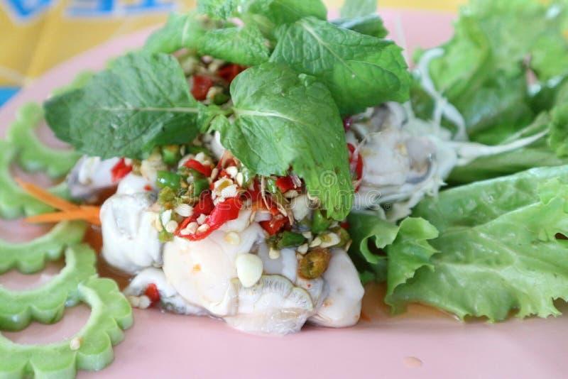 La ostra asada con la salsa del chile, de la cebolla, del limón y de pescados puso en una placa plástica imagen de archivo libre de regalías