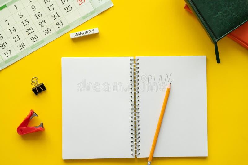 La página en blanco del cuaderno está encima de tabla del escritorio Visión superior, endecha plana imagen de archivo libre de regalías