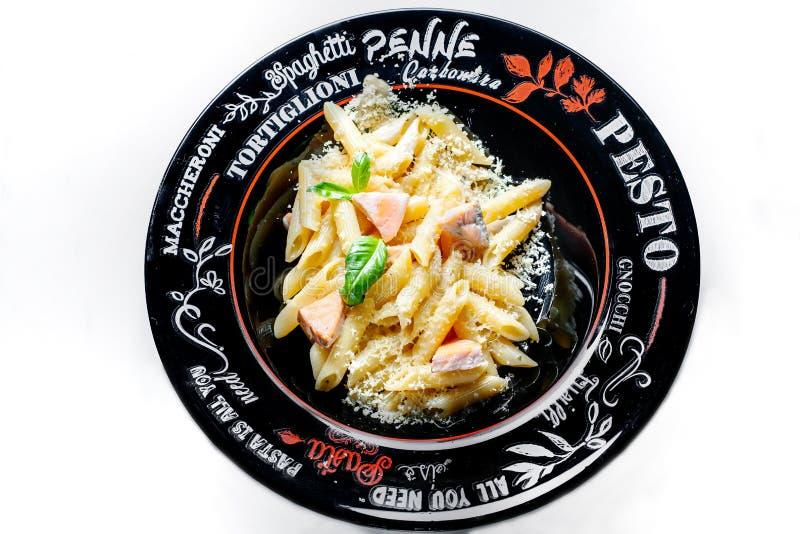 La pâte italienne en crème et avec un saumon, un basilic et le poivre cinq images libres de droits