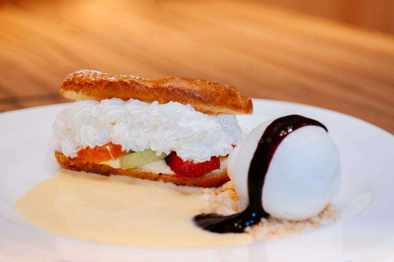 La pâtisserie cuite au four fraîche d'Eclair avec de la crème, fraise, crème glacée absorbent photo stock