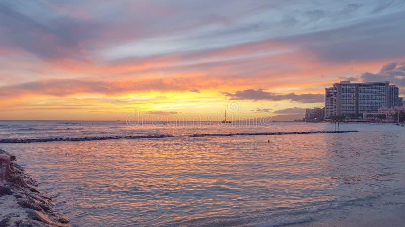 La pêche a coloré le coucher du soleil réfléchi sur l'eau à la plage de Waikiki images libres de droits