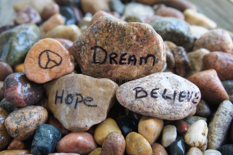 La pace, speranza, sogno e crede scritto a mano sulla roccia del fiume immagini stock