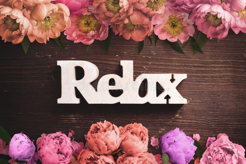 La pagina dei fiori su fondo di legno e il ` di parola si rilassano il ` immagini stock libere da diritti
