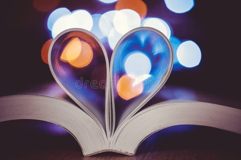 La pagina del libro decora a forma del cuore con la luce del bokeh della celebrazione per amore e romance del concetto del giorno fotografie stock