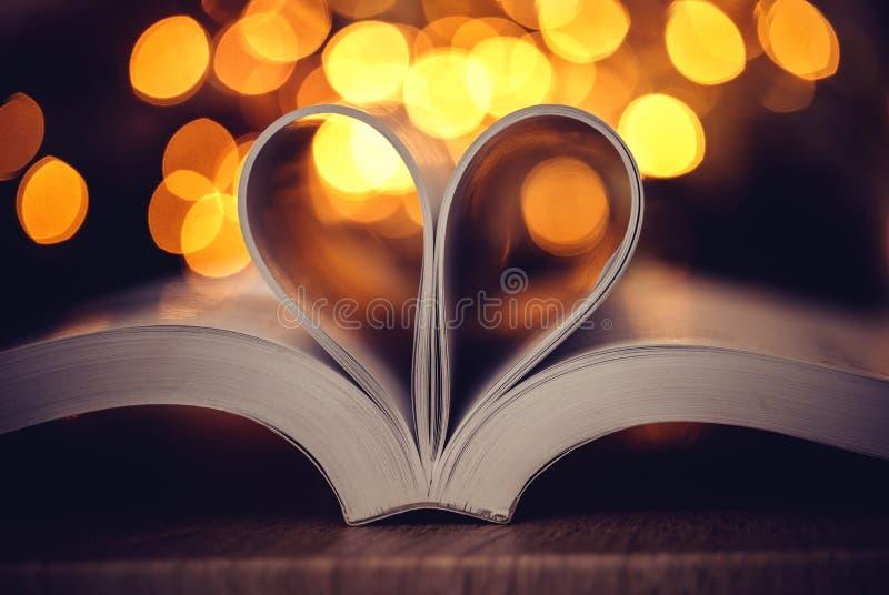 La pagina del libro decora a forma del cuore con la luce f del bokeh della celebrazione immagine stock