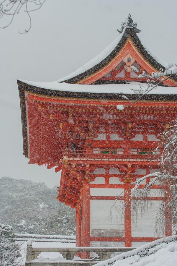 La pagoda rossa al tempio di Kiyomizu-dera con l'albero ha riguardato il fondo bianco della neve immagine stock libera da diritti