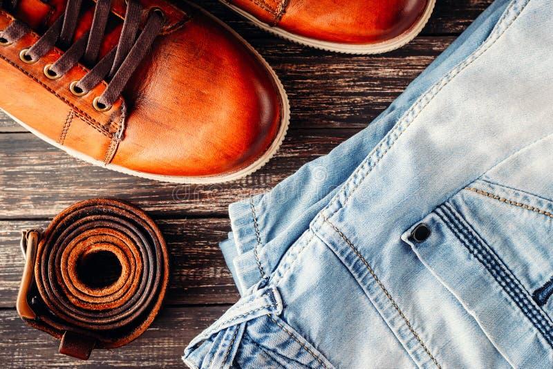 La paire du mâle en cuir brun chausse les blues-jean et le fond en bois foncé de ceinture, plan rapproché de vue supérieure photographie stock