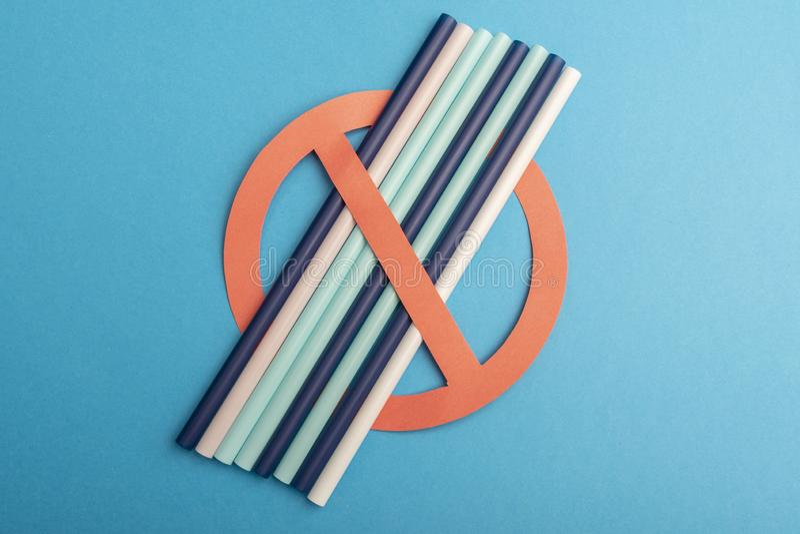 La paja plástica utilizó para el agua potable o los refrescos concepto de protesta en fondo azul ning?n pl?stico imágenes de archivo libres de regalías