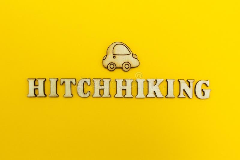 La palabra 'autoestop 'y la figura del coche en un fondo amarillo fotos de archivo libres de regalías