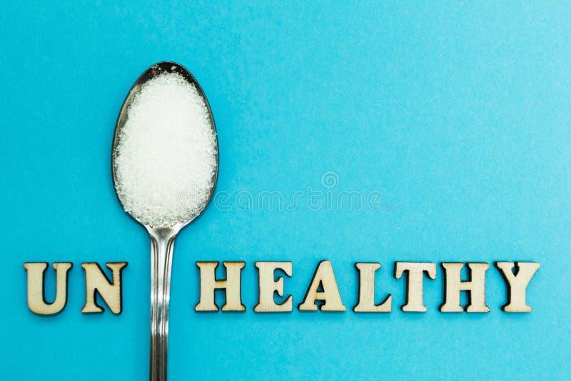 La palabra la 'O.N.U sana ', una cuchara con el azúcar en un fondo azul, concepto foto de archivo libre de regalías