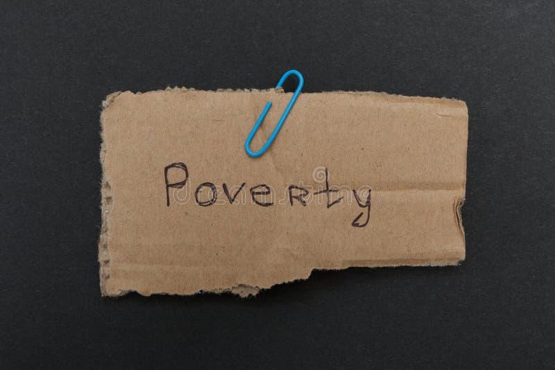 La palabra 'pobreza 'en la cartulina vieja foto de archivo