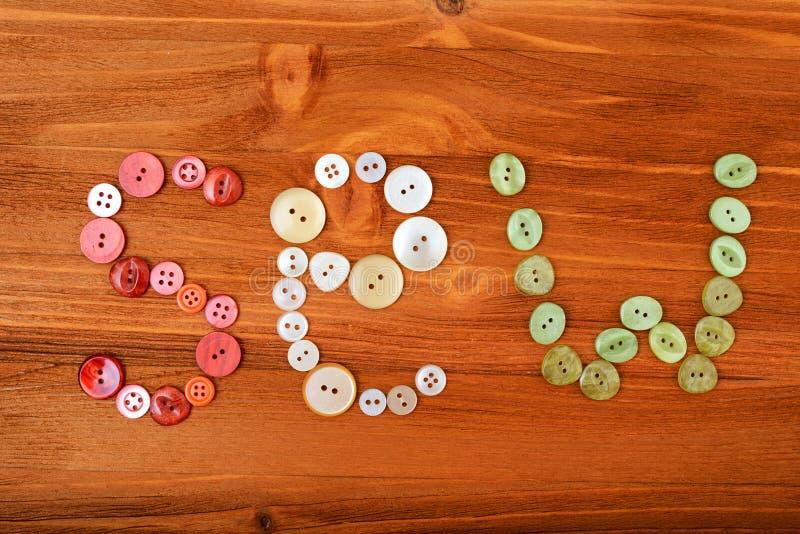 La palabra cose de los botones de costura multicolores en fondo de madera imágenes de archivo libres de regalías