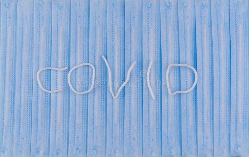 La palabra COVID en el fondo de máscaras protectoras quirúrgicas Cara de vendaje respiratorio médico imágenes de archivo libres de regalías